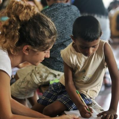 A volunteer works with children on English exercises in Sri Lanka on our project for high school students